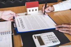 Estate agent broker reach contract form to client signing agreem royalty free stock photos