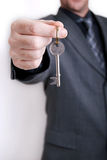 Estate agent business man. A real estate agent holds out the front door key of a new home to a lucky buyer Stock Photos