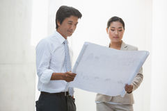 Estate agent and buyer looking at blueprint Royalty Free Stock Photo