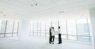 Estate agent with clients inside an empty office space. Wide angle shot of real estate agent with potential clients inside an empty office space. Estate broker stock photos