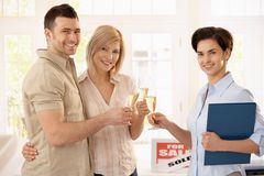 Estate agent congratulating couple. With champagne on purchasing new house stock image
