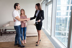 Estate agent congratulating young couple with property purchase,. Happy beautiful couple and friendly realtor handshaking making real estate deal after signing Royalty Free Stock Photo
