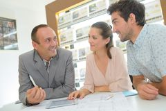 Estate agent in consultation with young couple royalty free stock images