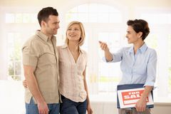 Estate agent and couple in new house. Happy couple checking new house with estate agent royalty free stock photos