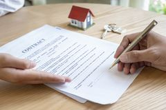 Estate agent with customer after contract signature of buying house. Loan, buying house, giving key royalty free stock photos
