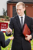 Estate agent gives keys to client Stock Photography