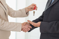 Estate agent giving house key to customer Stock Photo