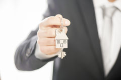 Estate agent giving house keys on a silver house shaped keychain.  Stock Photography