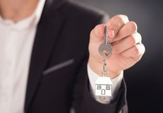 Estate agent giving house keys. On a silver house shaped keychain Stock Image