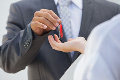 Estate agent giving the key to buyer. Outside new home Stock Images