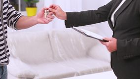 Estate agent giving key to couple stock video footage