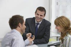 Estate Agent Handing Key To Couple Stock Image