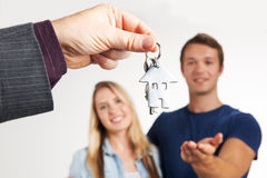 Estate Agent Handing Over House Keys To Young Couple Royalty Free Stock Photography