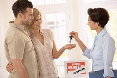 Estate agent handing over keys. Of new house to smiling couple Royalty Free Stock Images