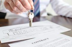 Estate agent holding house keys Stock Photos