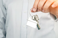 Estate agent holding keys to new house. Home shape chrome pendant Royalty Free Stock Image