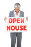 Estate agent holding and looking at sign for open house Stock Photo