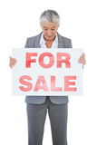 Estate agent holding and looking at sign for sale Stock Photography