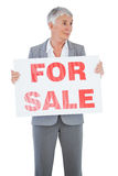 Estate agent holding sign for sale and looking away Stock Photo