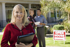 Estate Agent With House And Couple In Background Stock Photo
