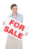 Estate agent posing with for sale sign. Against white background Royalty Free Stock Photography