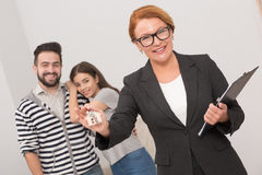 Estate agent is ready to hand over the keys of an apartment to new owners after signing the agreement. Royalty Free Stock Image