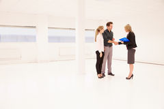 Estate Agent Shaking Hands With Clients In Empty Office Stock Photography