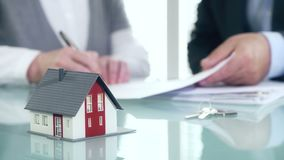 Businessman signs contract behind home architectural model stock footage