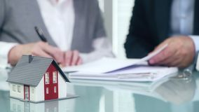 Businessman signs contract behind home architectural model stock video footage