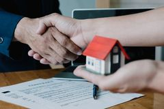 Estate agent shaking hands with his customer hand holding house royalty free stock image
