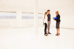 Estate Agent Showing Empty Office Space To Potential Clients Stock Photography