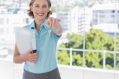 Estate agent showing house keys and smiling at camera. In a bright office stock images