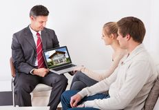 Estate agent showing laptop to couple. Estate Agent Showing House On Laptop To Young Couple Sitting At Home Royalty Free Stock Photography