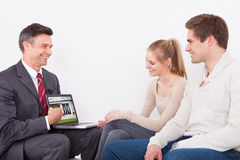 Estate Agent Showing Laptop To Couple Royalty Free Stock Image
