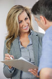 Estate agent showing lease to customer and smiling Royalty Free Stock Image