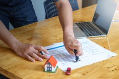 Estate agent stamping the document on wooden desk: real estate, home loan and insurance concept stock photo
