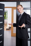 Estate agent stands at the entrance to apartment Stock Images
