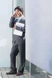 Estate agent talking on phone. Outside a house Royalty Free Stock Images