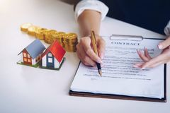 Estate agent use the pen pointing on document showing where to s stock images