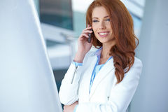 Estate agent woman on the phone. A beautiful young real estate agent woman on the phone Royalty Free Stock Image