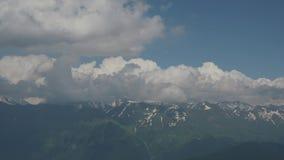 Estate al rallentatore Picchi di montagna di Snowy contro un fondo delle nuvole bianche e di un cielo blu Viaggio alle montagne video d archivio