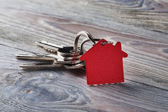 Estate concept with key, red keychain with house symbol. Estate concept with key, red keychain with a house symbol Stock Photo