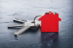 Estate concept with key, red keychain with house symbol, concrete Stock Photos