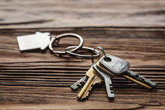 Estate concept, keychain with house symbol, key on wooden background Stock Photos