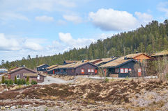 The estate cottages in the mountains of Norway. Gautefall, Norway - May 2, 2015:  Brown, black wooden residential houses. Green roof. Early spring, around the Stock Photography