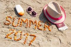 Estate 2017 dell'iscrizione, accessori per prendere il sole e passaporto con il dollaro di valute sulla sabbia alla spiaggia, ora Fotografie Stock Libere da Diritti