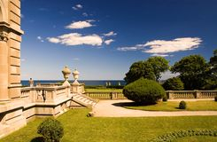 Estate patio and garden. A view across the lawn and garden at the side patio of a beautiful, luxury estate.  This is the famous Vanderbilt Breakers mansion in Stock Photos