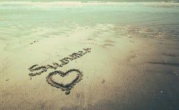 Estate scritta a mano nella sabbia della spiaggia con un cuore adorabile Fotografia Stock