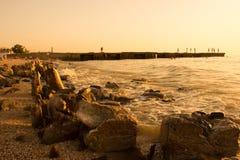 Estate, tramonto della spiaggia dal mare Nei precedenti, un frangiflutti da cui la gente salta nella ram Sulle pietre enormi ante Immagine Stock Libera da Diritti