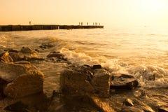 Estate, tramonto della spiaggia dal mare Nei precedenti, un frangiflutti da cui la gente salta nella ram Sulle pietre enormi ante Fotografia Stock Libera da Diritti